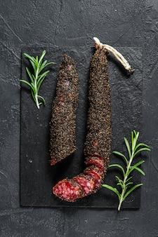 Fuet, salami und ein rosmarinzweig. traditionelle spanische wurst. schwarzer hintergrund. ansicht von oben
