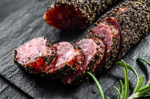 Fuet, salami und ein rosmarinzweig.