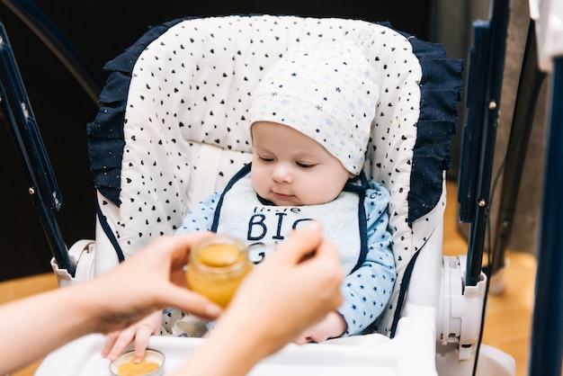Füttern. entzückendes baby, das mit einem löffel im hochstuhl isst. baby