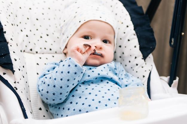 Füttern. entzückendes baby, das mit einem löffel im hochstuhl isst.