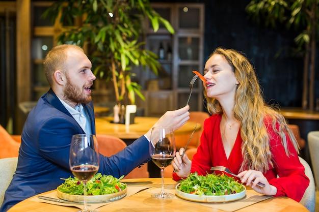 Fütterungsfrau des mannes mit salat im restaurant