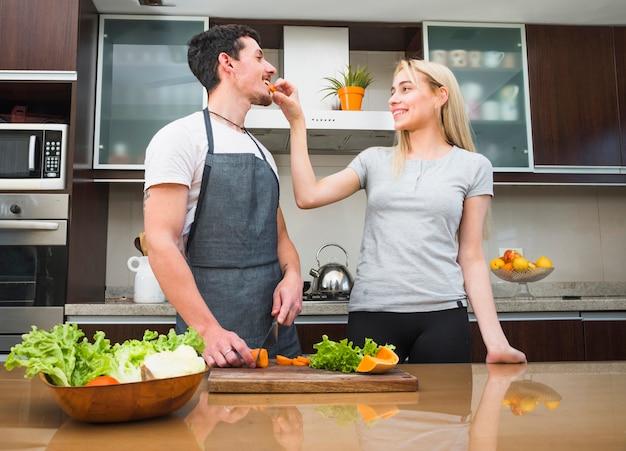 Fütterungskarottenscheibe der jungen frau zu ihrem ehemann in der küche