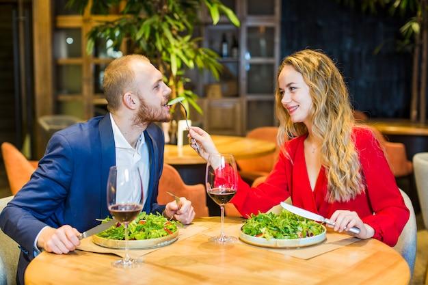 Fütterungsmann der jungen frau mit salat im restaurant