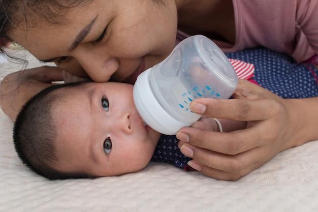 Fütterungsmilch der mutter und küssen ihr baby
