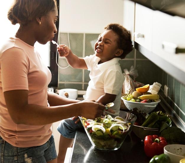 Fütterungsmutter des schwarzen kindes mit dem kochen des lebensmittels in der küche