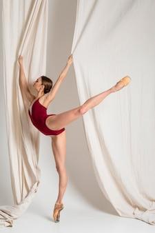 Full shot ballerina auf einem bein stehend