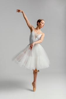 Full shot ballerina stehend mit spitzenschuhen