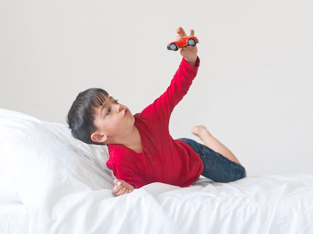 Full shot boy mit spielzeug im bett Kostenlose Fotos