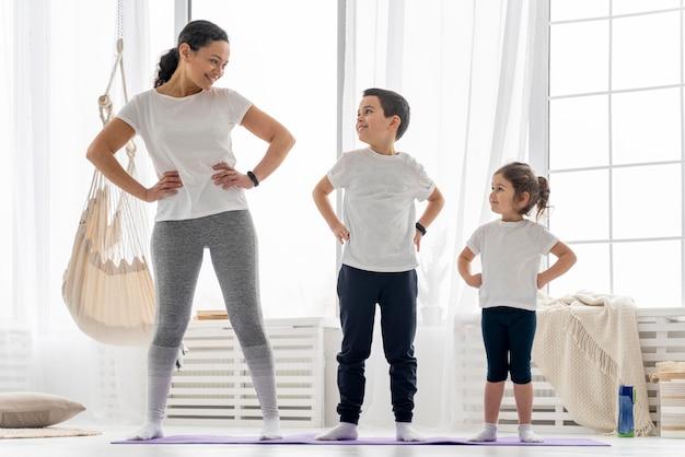 Full shot erwachsene und kinder auf yogamatte