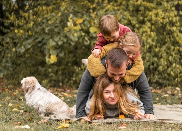Full shot familie, die spaß mit hund hat