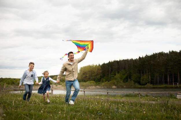 Full shot familie mit regenbogendrachen