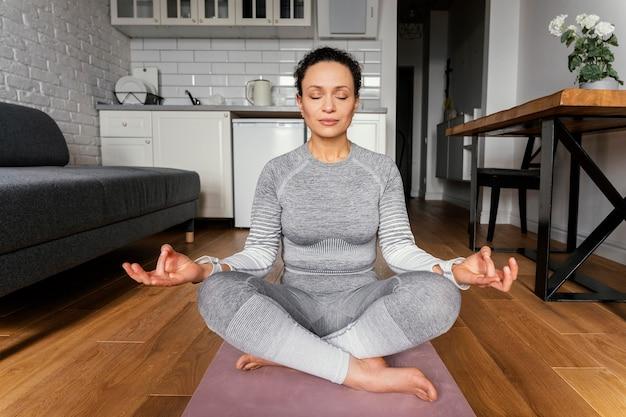 Full shot frau auf yogamatte