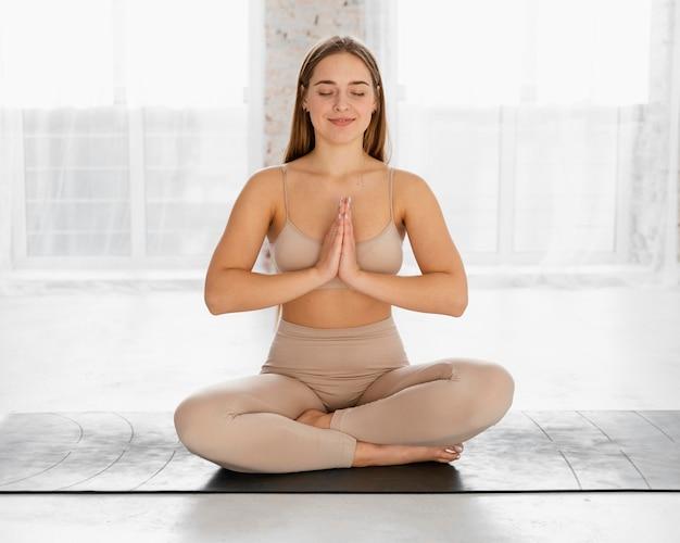 Full shot frau meditiert auf matte