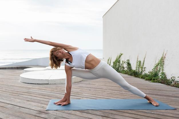 Full shot frau praktiziert yoga auf matte im freien