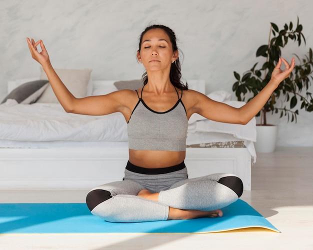 Full shot frau praktiziert yoga