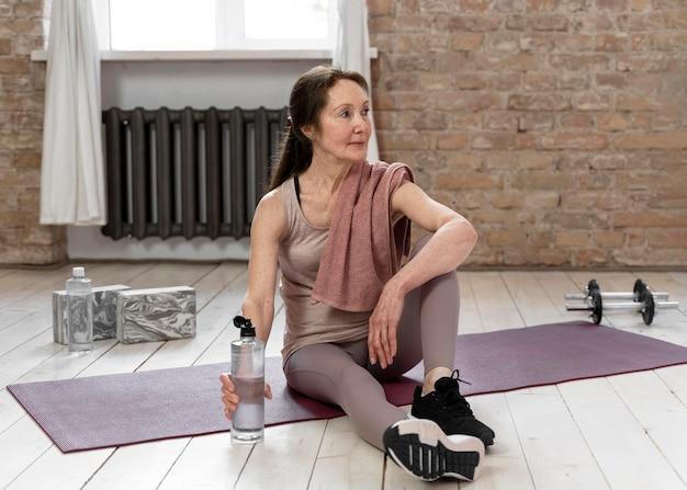 Full shot frau sitzt auf yogamatte