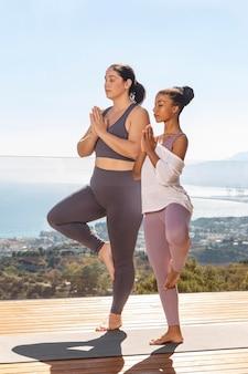 Full shot frauen, die zusammen yoga machen
