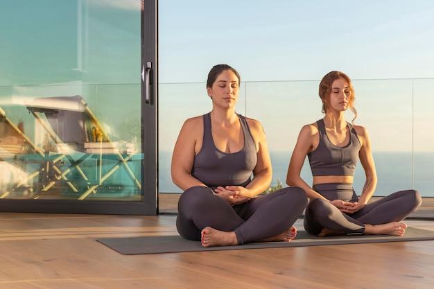 Full shot frauen sitzen auf yogamatte