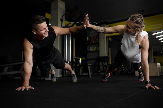 Full-shot-freunde trainieren im fitnessstudio