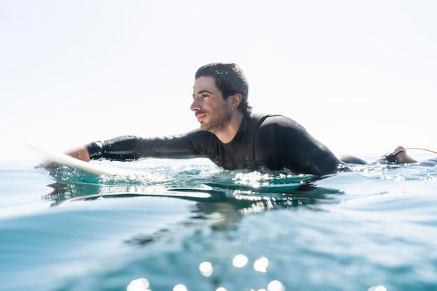 Full shot junger mann beim surfen