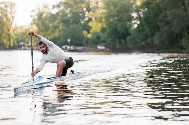 Full shot junger mann paddeln