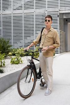 Full shot kerl hält fahrrad