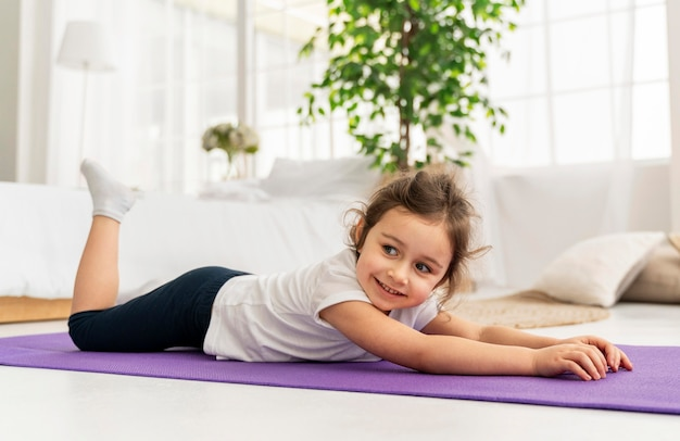 Full shot kind auf yogamatte