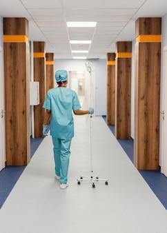 Full shot krankenschwester geht auf halle