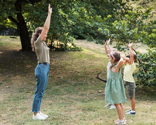 Full shot lehrer und kinder mit erhobenen händen