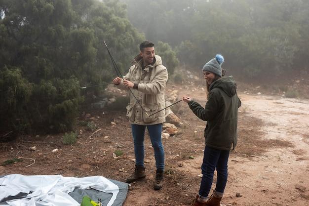 Full shot leute bauen ein zelt auf