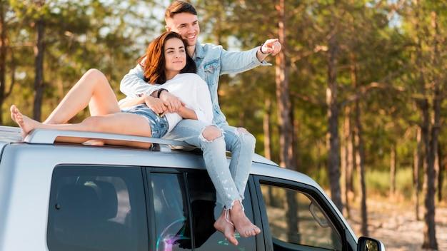 Full shot leute sitzen auf dem auto