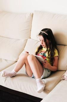 Full shot mädchen sitzt auf der couch mit ihrem tablet