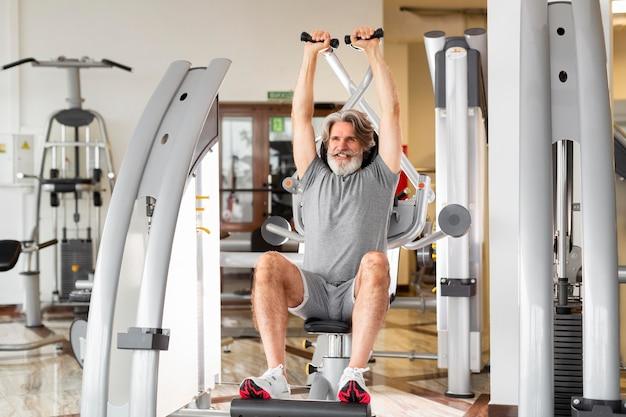 Full shot mann arbeitet im fitnessstudio
