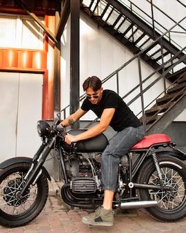 Full shot mann auf altem motorrad