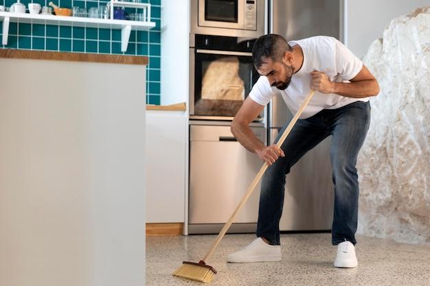 Full shot mann, der die küche putzt