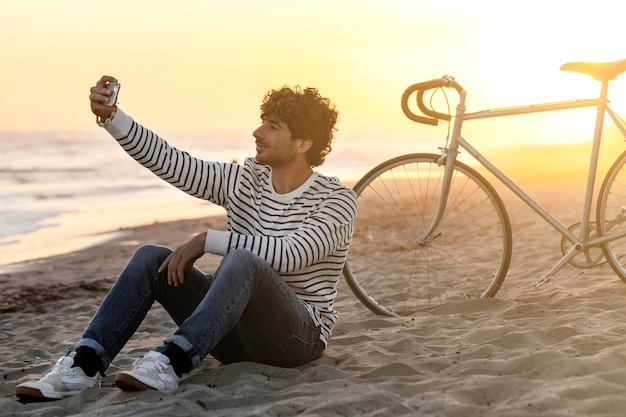 Full shot mann, der selfie am strand nimmt
