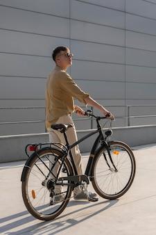 Full shot mann hält fahrrad
