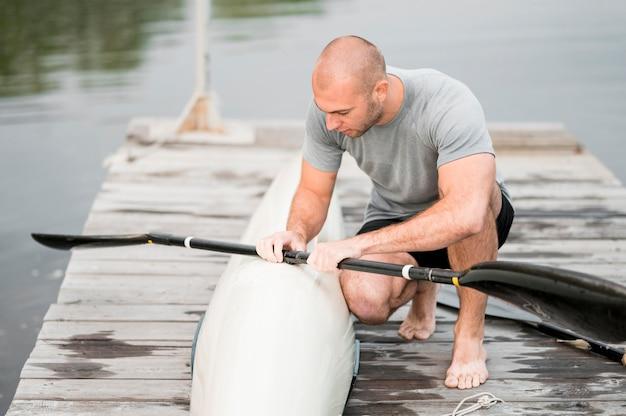 Full shot mann hält paddel