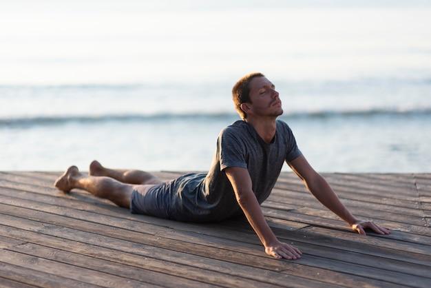 Full shot mann macht yoga in der nähe von meer