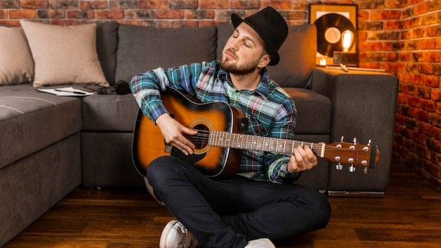 Full shot mann mit hut spielt gitarre