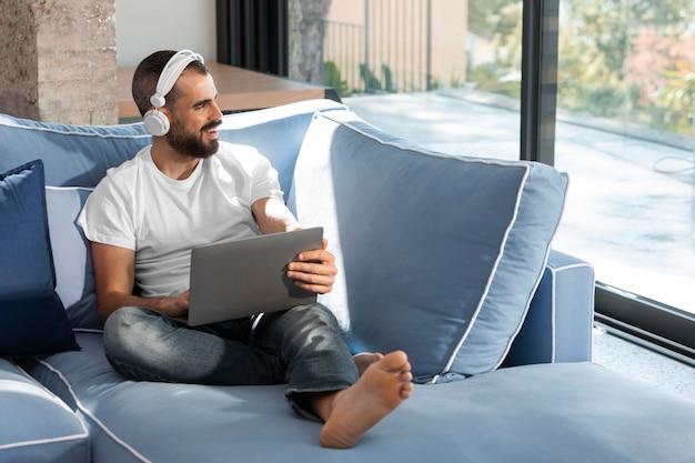 Full shot mann mit kopfhörern und laptop