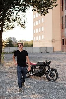 Full shot mann mit motorrad im freien