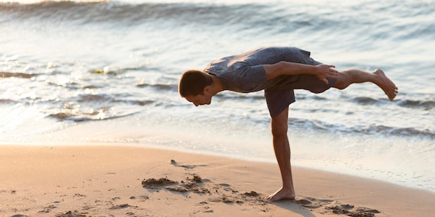 Full shot mann praktiziert yoga mit dem meer dahinter