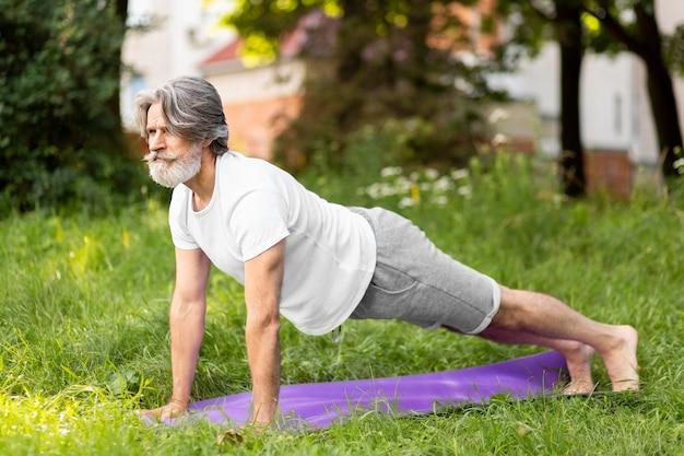 Full shot mann praktiziert yoga