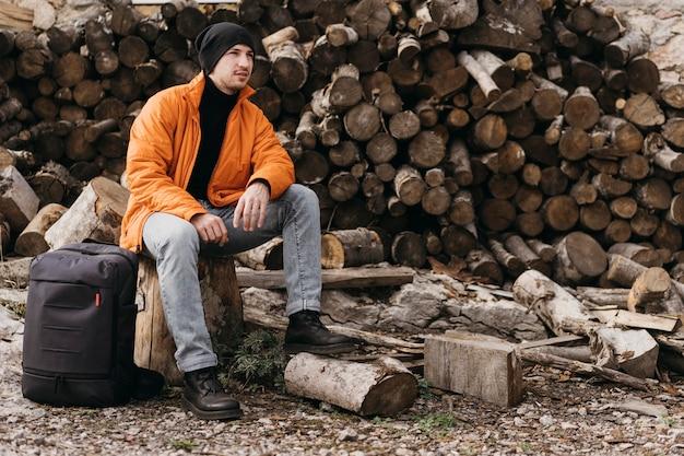 Full shot mann sitzt auf stumpf