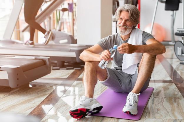 Full shot mann sitzt auf yogamatte
