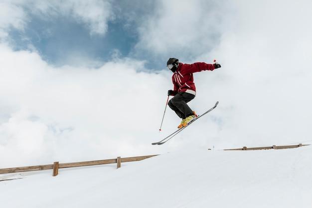 Full shot skifahrer springen