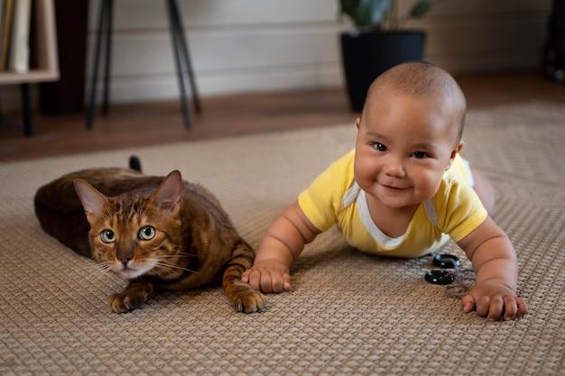 Full shot smiley baby und katze auf dem boden Premium Fotos