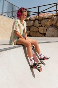 Full shot smiley-frau mit skateboard