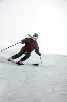 Full shot smiley frau skifahren im freien